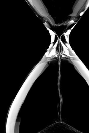 out time: Sand flowing through an hourglass on black background concept for time running out Stock Photo