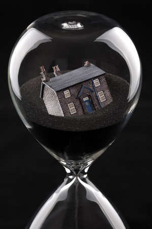 foreclose: hourglass with house sinking into sand concept for housing market recession or housing difficulties Stock Photo