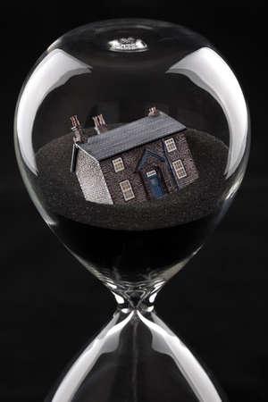 reloj de arena: reloj de arena con la casa que se hunde en la arena concepto de recesión del mercado de la vivienda o las dificultades de vivienda
