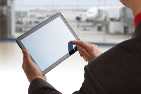Businessman finger touching screen of a digital tablet at the departure gate of an airport photo