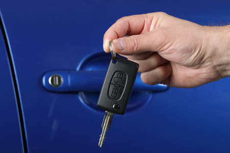Car salesman or rental man giving a car key to a customer photo