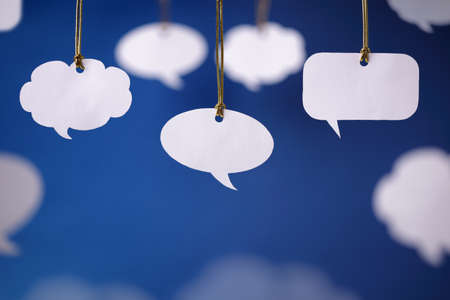 Blank white speech bubbles hanging from a cord Stock Photo