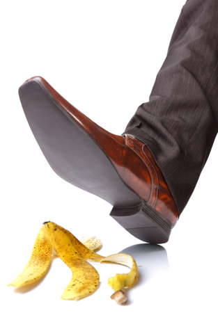 Businessman foot about to slip and fall on a banana skin photo