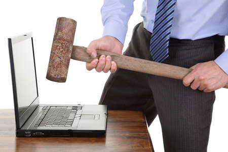 Businessman with a sledgehammer ready to smash his laptop computer concept for frustration, failure or stress  photo