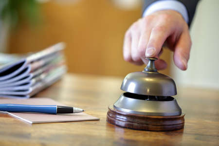 complaining: Businessman ringing a hotel reception service bell to attract attention