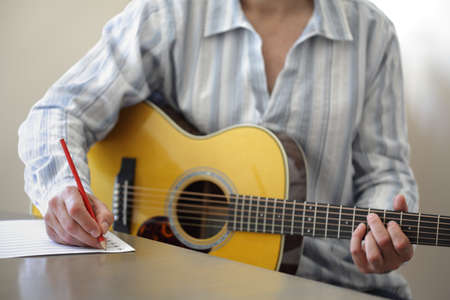 fretboard: Guitarist musician writing a song on his guitar