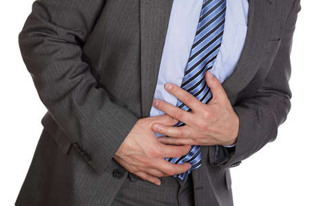 bent over: Businessman holding his stomach in pain or indigestion Stock Photo