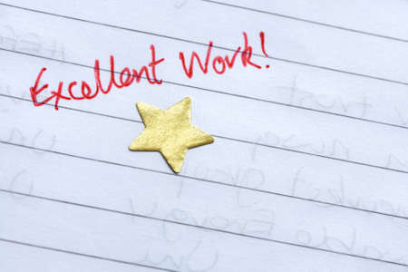 excellent work: Excellent work gold star award on notepad Stock Photo