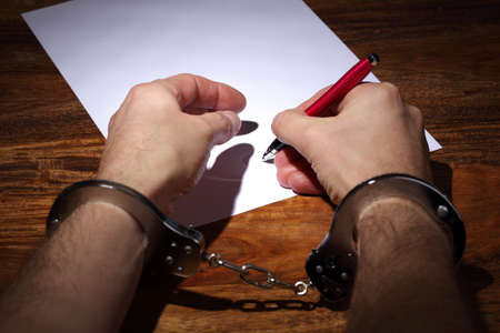 Man in handcuffs signing a document concept for coercion or being pressured into giving a signature or marriage photo