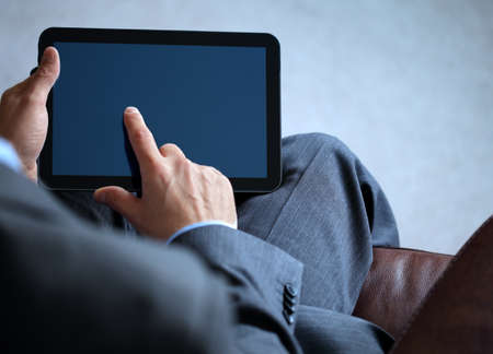 tablet pc: Businessman with finger touching screen of a digital tablet whilst sitting on a sofa