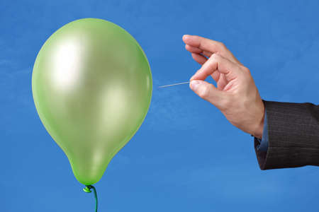 popping: Needle about to pop a green balloon Stock Photo