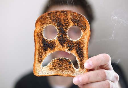 quemado: Hombre que soporta una rebanada de pan tostado quemado con un conept sonriente infeliz por mal comienzo para el d�a