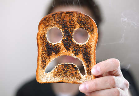 conept: Man holding up a burnt slice of toast with an unhappy smiley conept for bad start to the day