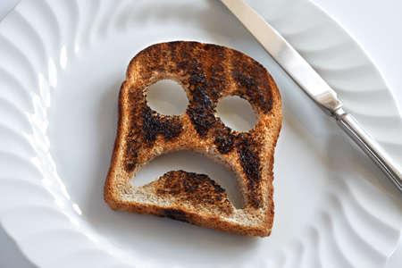 occhi tristi: Smiley triste e infelice a base di pane tostato con coltello e piatto