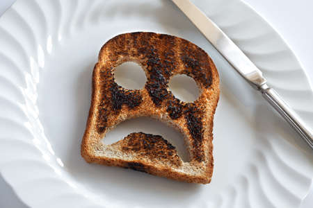 cara triste: Smiley triste e infeliz hecha de pan tostado con cuchillo y plato