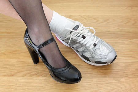 work life balance: Woman wearing one business shoe and sports shoe concept for work-life balance, healthy lifestyle and wellbeing choice