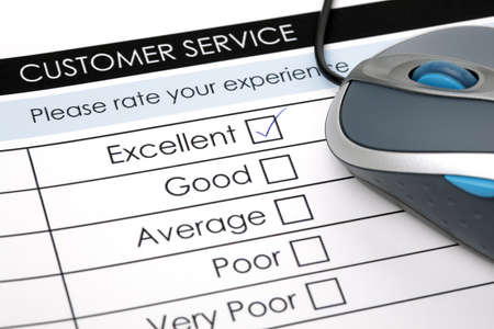 online survey: Tick placed in excellent checkbox on customer service satisfaction survey form with computer mouse Stock Photo