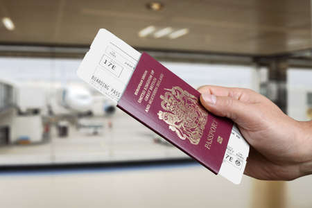 tickets: Handing over boarding pass and passport to embark on a flight in an airport Stock Photo