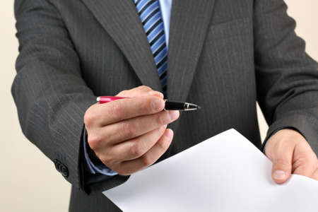 requesting: Businessmans hand holding a pen requesting a signature on a document