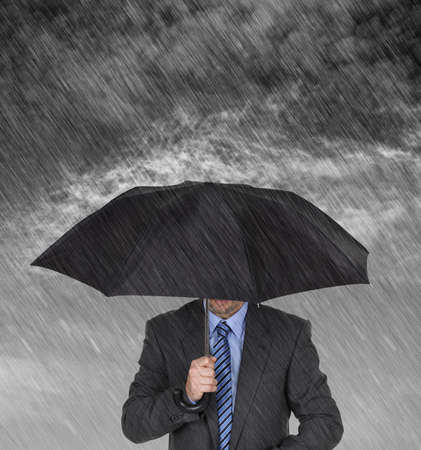 Businessman with umbrella protecting himself from the storm concept for protection from recession or economic depression etc photo