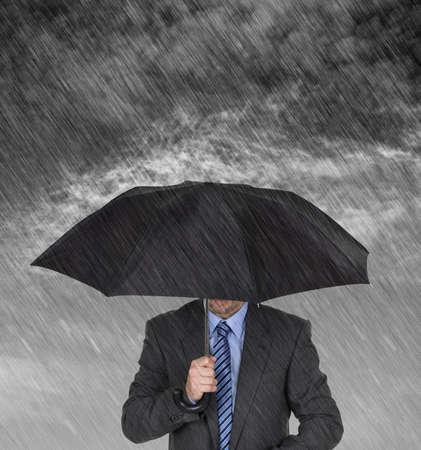 crisis economica: Hombre de negocios con el paraguas protegiendo a sí mismo a partir del concepto de tormenta para la protección de la recesión o depresión económica, etc