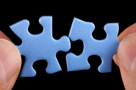 two pieces: Hands holding two pieces of blue puzzle and fitting them together concept for solution or partnership Stock Photo