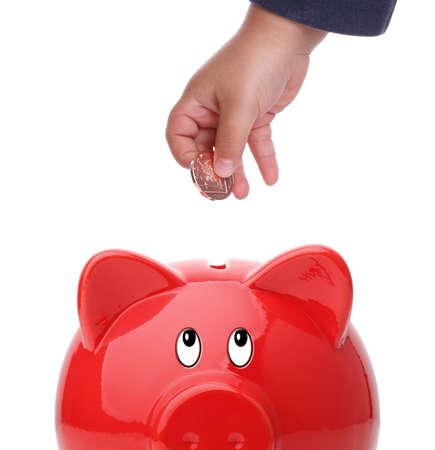 Baby boy putting coin into a piggy bank photo