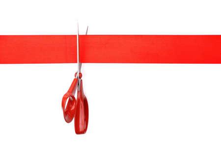 Schaar die rood lint of tape tegen witte