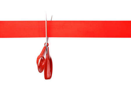 Scissors cutting red ribbon or tape against white  photo