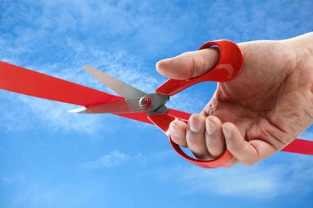 Podnikatel řezání červenou stuhou s nůžkami Reklamní fotografie