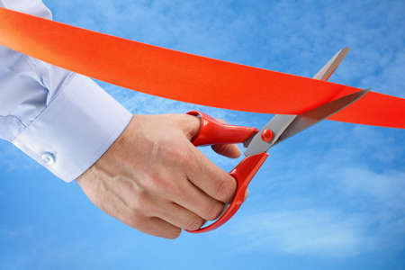 Businessman cutting a red ribbon with a pair of scissors photo