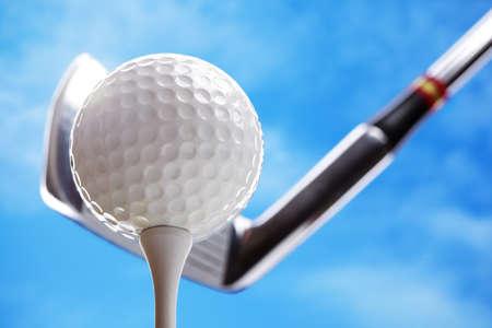 Golfclub en golfbal op het punt om de tee-off tegen een blauwe hemel Stockfoto