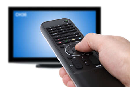 remote control: Hand using tv remote control to change channels on defocused television