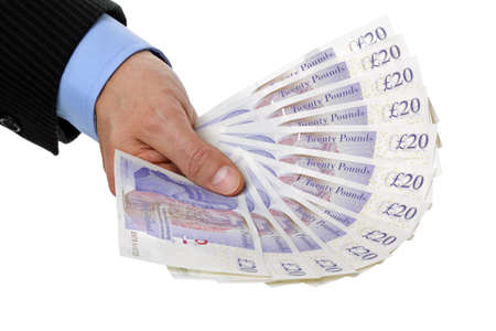 british money: Businessman hand holding twenty pound notes against white  Stock Photo