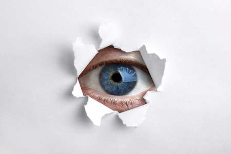 Mans eye peeking through a hole in white paper