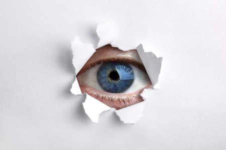 Mans oog gluren door een gat in wit papier