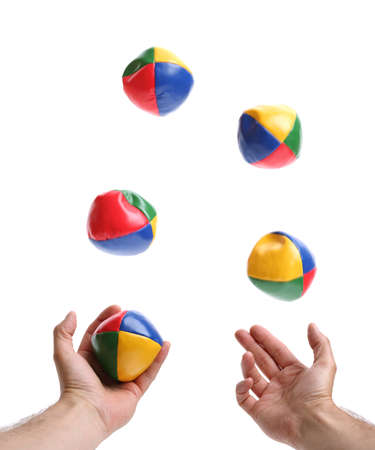 Concept for juggling priorities, 5 balls being thrown by pair of hands over white blurred motion on balls Stock Photo