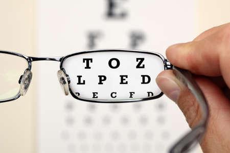 vision test: Mirando a trav�s de lentes en una carta del examen de ojo