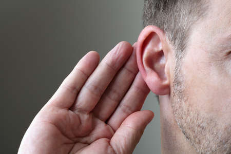 attention: Close up on hand and ear listening for a quiet sound or paying attention Stock Photo