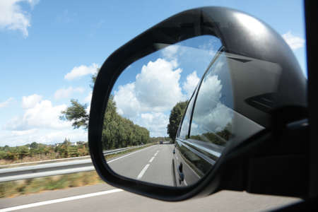 Rear view mirror reflecting road, sky and traffic