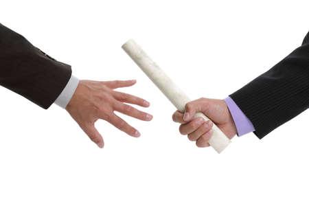 Partnership or teamwork concept two men handing over a paaperwork baton photo