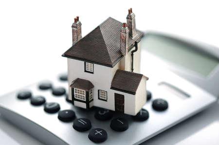 Huis rustend op calculator concept voor de hypotheek calculator, thuis financiën of sparen voor een huis Stockfoto
