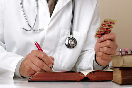 medical notes: Doctor holding pills writing patient notes on a medical examination form or prescription Stock Photo