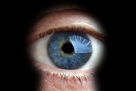 big brother spy: Mans eye looking through a blured keyhole Stock Photo