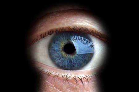 big brother spy: Mans ojo que mira a trav�s de un ojo de la cerradura borroneada Foto de archivo