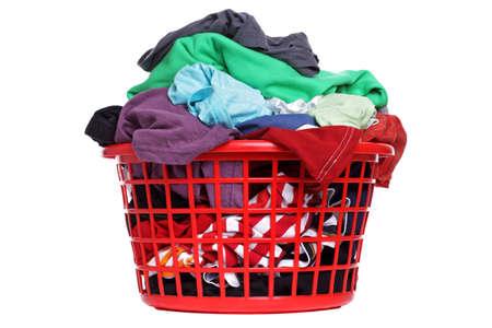 launderette: Colorful clothes in a red laundry basket on white background Stock Photo