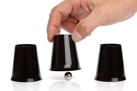 Cup and ball guessing game success with hand revealing the correct cup
