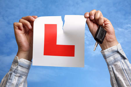 letter l: Tearing L plate against a sky holding a car key after passing driving test Stock Photo