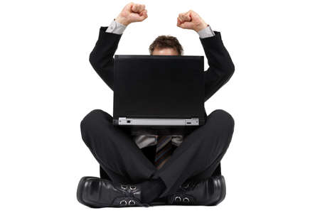 Businessman sitting on the floor with legs crossed celebrating news of success on his laptop photo