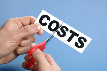 cutting costs: Scissors cutting the word costs concept for recession or credit crisis